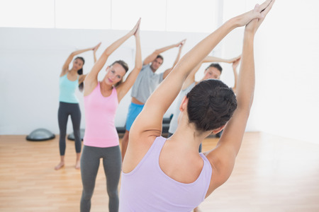 Sporty class and instructor with joined hands in the fitness studio