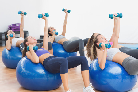 Fit class and instructor exercising with dumbbells on fitness balls in gym