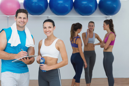Portrait of a smiling couple with fitness class in background at gym