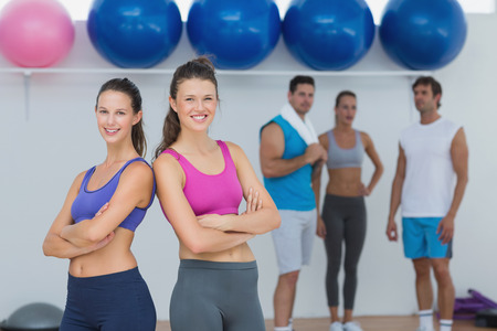 Portrait of fit young women in sports bra with friends in background in fitness studio