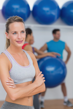 Portrait of a fit smiling young woman with friends in background at fitness studio