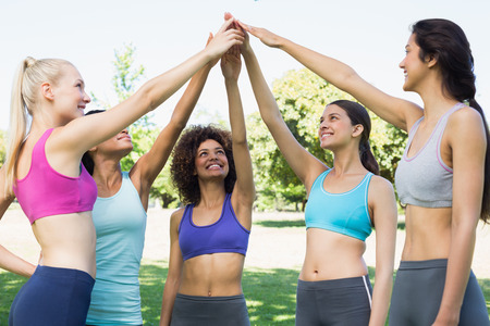 Happy young women in sportswear raising hands together in park