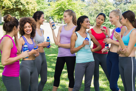 Multiethnic sporty women with water bottles communicating at park