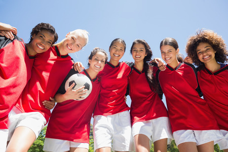 Portrait of confident female soccer team with ball against clear blue sky