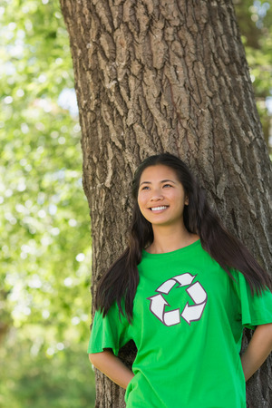 Portrait of a smiling young woman wearing green recycling t-shirt in the park