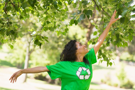 View of a young woman in green recycling t-shirt touching leaves at the park