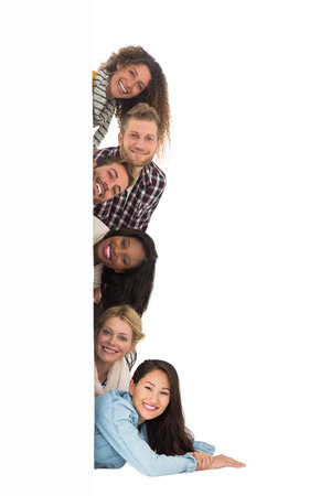 Photo pour Happy group of young friends peeking from behind a wall on white background - image libre de droit