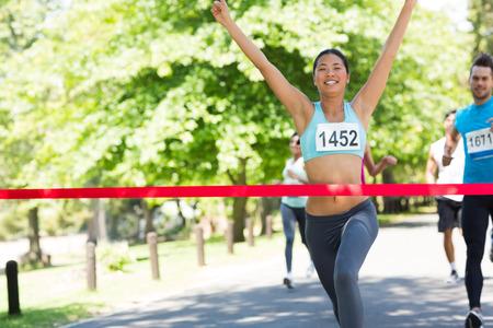 Female marathon winner with arms raised crossing finish line