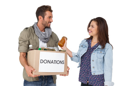 Portrait of a smiling young couple with donation box over white background