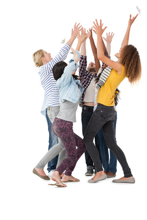 Group of casually dressed happy young people raising hands over white background