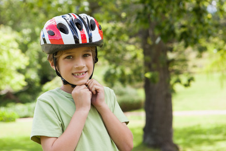 Portrait of a smiling young boy wearing bicycle helmet at the park