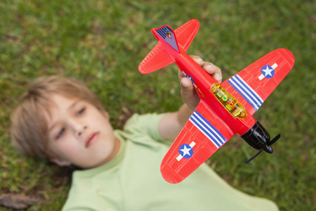 Young boy playing with a toy plane at the park