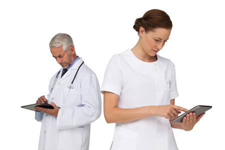 Male and female doctors using digital tablets over white background