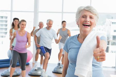 Foto de Cheerful senior woman gesturing thumbs up with people exercising in the background at fitness studio - Imagen libre de derechos