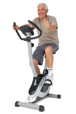 Photo pour Full length of a senior man gesturing thumbs up on stationary bike over white background - image libre de droit