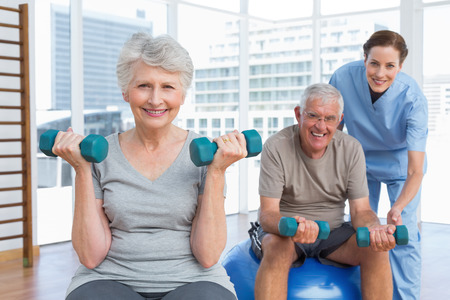 Female therapist assisting senior couple with dumbbells in the medical officeの写真素材