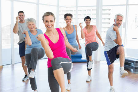 Foto de Portrait of smiling people doing power fitness exercise at yoga class in fitness studio - Imagen libre de derechos
