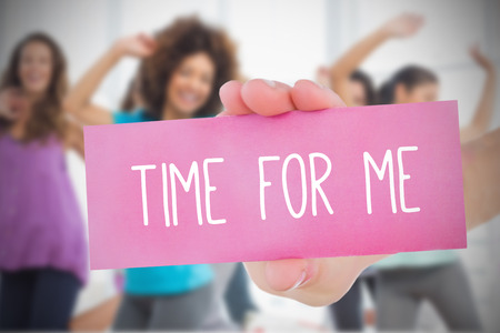 Woman holding pink card saying time for me against dance class in gym
