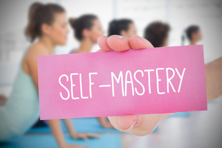 Woman holding pink card saying self mastery against yoga class in gym