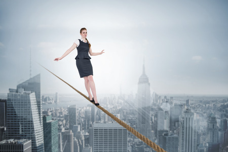 Composite image of businesswoman doing a balancing act against cityscape