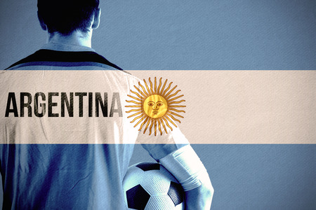 Argentina football player holding ball against argentina national flag