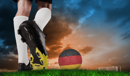 Composite image of football boot kicking germany ball against green grass under blue and orange sky