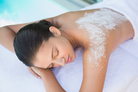 Calm brunette lying on towel with salt treatment on back outside at the spa