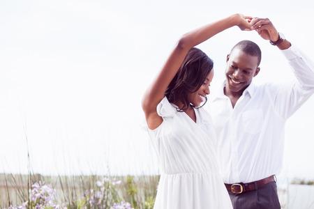 Foto de Romantic couple dancing and smiling outside in the garden - Imagen libre de derechos
