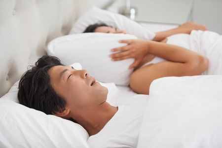 Woman covering her ears as partner is snoring loudly at home in bedroom