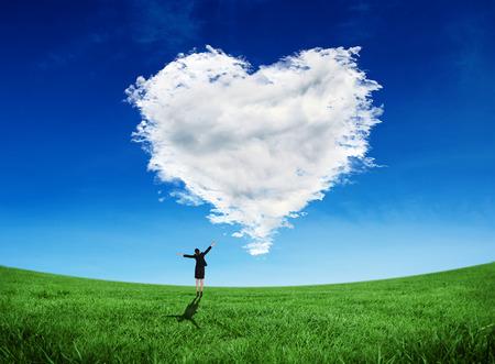Photo pour Composite image of excited businesswoman cheering against cloud heart - image libre de droit