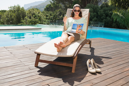 Beautiful young woman reading book on sun lounger by swimming pool