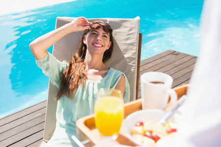 Smiling young woman looking at cropped waiter with breakfast tray by the pool