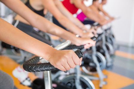 Spin class working out in a row at the gym