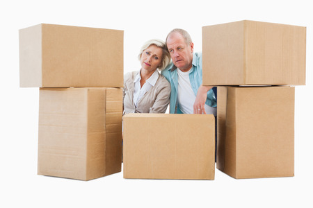 Stressed older couple with moving boxes on white backgroundの写真素材