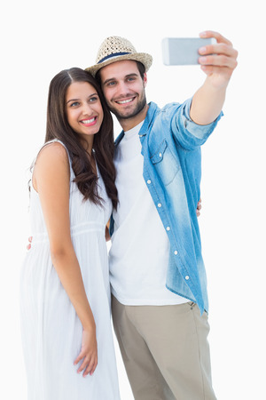 Happy hipster couple taking a selfie on white backgroundの写真素材