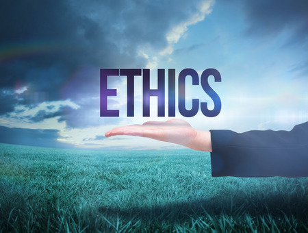 Businesswomans hand presenting the word ethics against blue sky over green field
