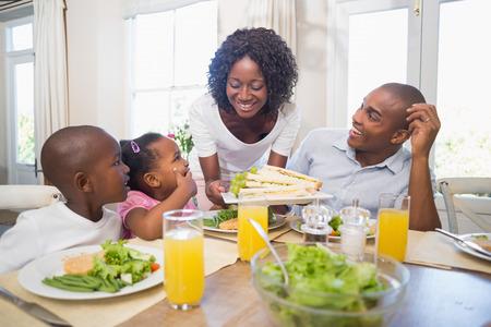 Foto de Happy family enjoying a healthy meal together at home in the kitchen - Imagen libre de derechos