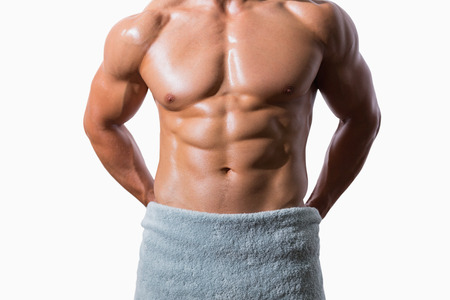 Mid section of a shirtless muscular man wrapped in white towel over white background