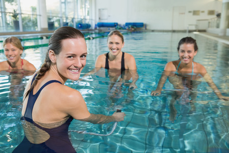 Photo pour Female fitness class doing aqua aerobics on exercise bikes in swimming pool at the leisure centre - image libre de droit