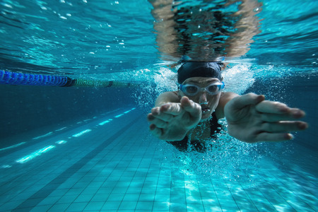 Photo pour Athletic swimmer training on her own in the swimming pool at the leisure centre - image libre de droit