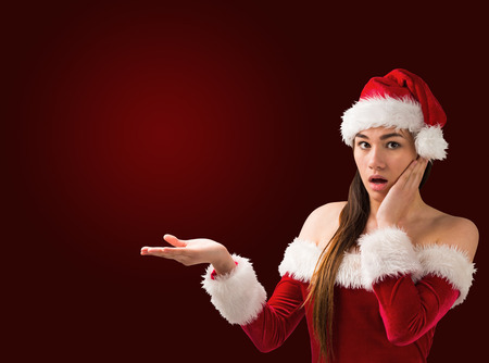Surprised brunette in santa outfit presenting with hand on red vignette backgroundの写真素材