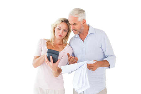 Anxious couple working out their bills on white background