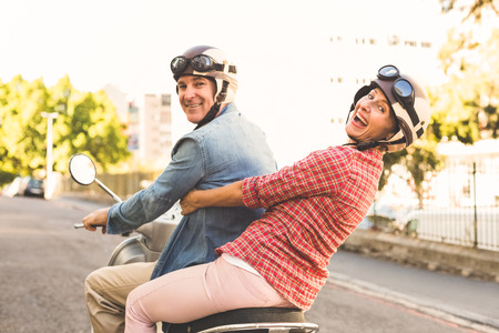 Foto per Happy mature couple riding a scooter in the city on a sunny day - Immagine Royalty Free