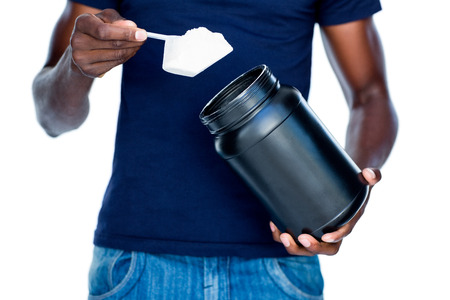 Mid section of a man holding a scoop of protein mix over white background
