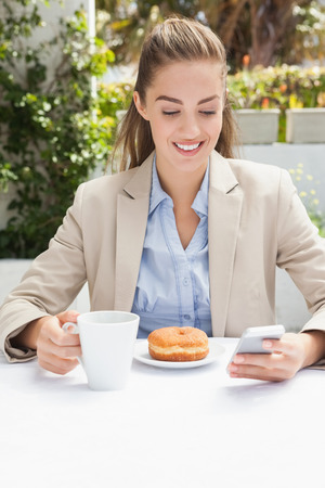 Beautiful businesswoman having a coffee and muffin outside at the coffee shop