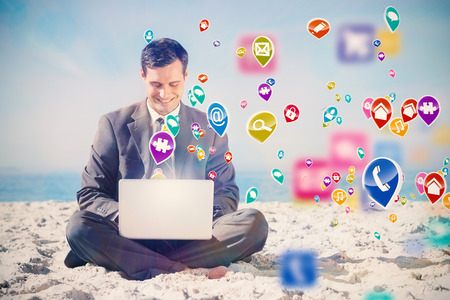 Young businessman with legs crossed typing on his laptop with colourful computer applications
