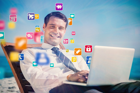 Cheerful young businessman lying on a deck chair with his computer with colourful computer applications