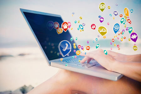 Woman sitting on beach using her laptop with colourful computer applications