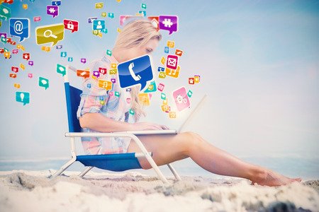 Pretty blonde sitting on beach using her laptop with colourful computer applications