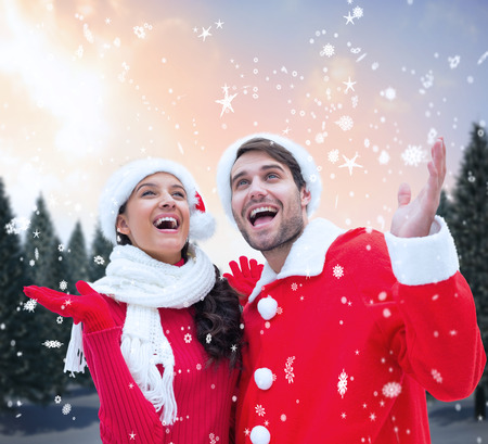 Festive young couple against snowy landscape with fir trees